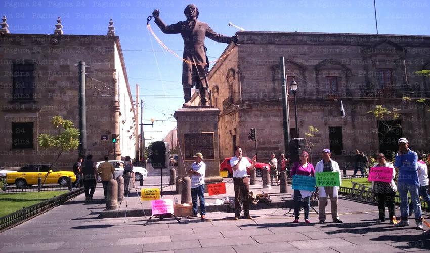 Alrededor de 30 personas hicieron un plantón simbólico en el monumento a Miguel Hidalgo y Costilla en la Plaza de la Liberación, lugar en el que se representa la abolición de la esclavitud; ahí, los inconformes, unieron las cadenas que el cura Hidalgo está rompiendo, en señal del retroceso del que acusan al gobierno federal/Fotos: Francisco Tapia
