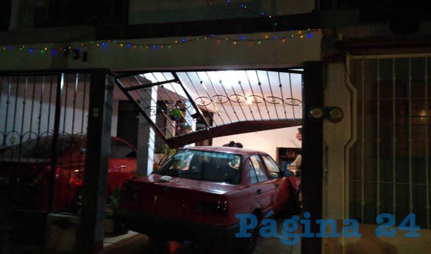 El auto Nissan Tsuru terminó dentro de la cochera luego de embestir el barandal