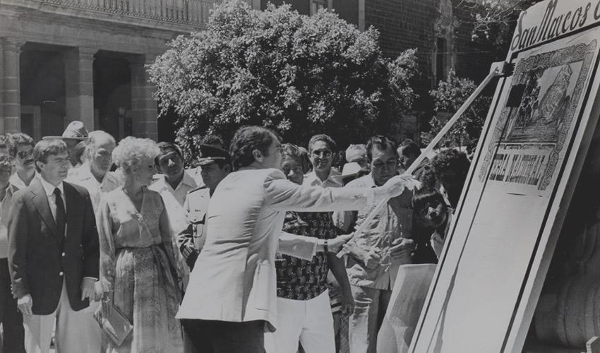 Ante el gobernador Rodolfo Landeros Gallegos (1980-1986) y su esposa Azul Landeros, el presidente municipal Miguel Romo Medina (1984-1986) fija uno de los bandos solemnes de la Feria Nacional de San Marcos (Fuente: Archivo Municipal de Aguascalientes)